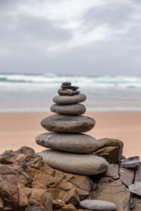 well balanced stone cairn on a lonely beach at the wild west coast of the portuguese algarve