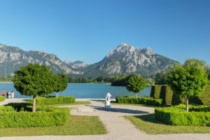Park at the Festspielhaus with a view over Forgensee to Hohenschwangau Castle and the Tannheimer Mountains, Allgäu, Swabia, Upper Bavaria, Germany