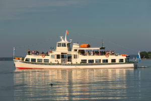 Excursion boat on the Chiemsee in front of the Fraueninsel at sunset, Upper Bavaria, Germany