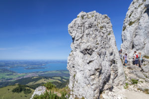 Bergsteiger am Aufstieg zum Gipfel der Kampenwand dahinter der Chiemsee, Aschau, Chiemgauer Alpen, Chiemgau, Oberbayern, Bayern, Süddeutschland, Deutschland, Europa