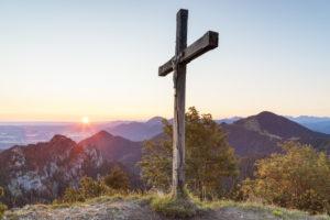 Sonnenaufgang am Gipfelkreuz des Sulten dahinter die Chiemgauer Alpen mit der Gedererwand und Hochplatte, Chiemgau, Oberbayern, Bayern, Süddeutschland, Deutschland, Europa