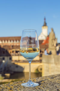 Glass of wine with a view over the Main to the old town of Würzburg, Lower Franconia, Franconia, Bavaria, Germany