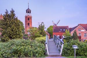Backsteinkirche und Fußgängerbrücke von Ditzum, Fischerdorf an der Unterems in Ostfriesland, Rheiderland, Niedersachsen, Norddeutschland, Deutschland, Europa