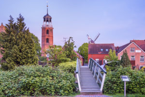 Brick church and footbridge of Ditzum, fishing village on the Unterems in East Friesland, Rheiderland, Lower Saxony, Northern Germany, Germany, Europe