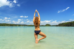 Woman doing yoga in the Osterseen, Iffeldorf, Upper Bavaria, Bavaria, Southern Germany, Germany, Europe