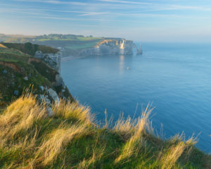 Coastline with cliffs at sunrise, Etretat, Seine-Maritime Department, Atlantic Ocean, Normandy, France