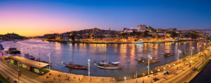 Panorama of Porto with the Dom Luiz bridge and traditional port wine transport boats, Portugal