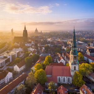 Altstadt von Hannover an einem nebligen Herbstmorgen mit der Kreuzkirche im Vordergrund und der Marktkirche und dem Rathaus im Hintergrund