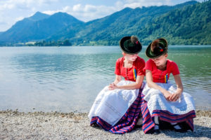 Two girls in traditional costumes of Schliersee on the shore of Lake Schliersee at the annual church day
