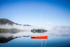 Sailboat on the Schliersee in Fischhausen in the morning fog