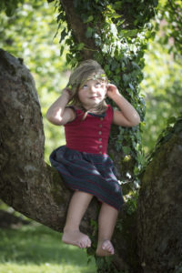 Child with ivy tendril around its head, sitting in an apple tree