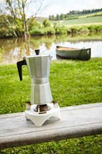 Espressokanne auf einem Campingkocher, im Hintergrund ein Kanu im Fluss