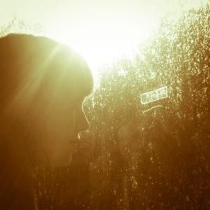 Junge Frau schaut aus dem Fenster,