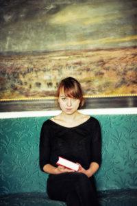 Junge Frau mit Buch auf grünen Sofa,