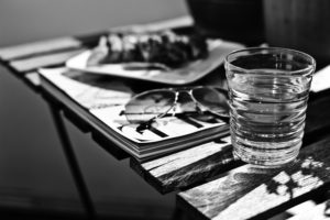 Glas Wasser in der Sonne auf Holztisch,