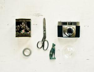 Schere, Kamera, Teedose, Katze, Vase auf weißer Tischplatte,