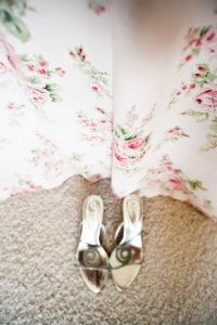 Silberne Schuhe vor einem Vorhang mit Rosendekor,