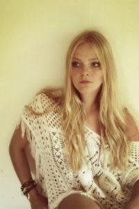 Junge Frau mit langen blonden Haaren sitzend an einer Wand,