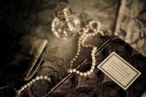 Stillleben mit Flacon und Perlenkette,
