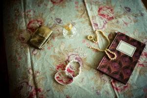 Stillleben mit Flacon, Perlenkette und Buch,