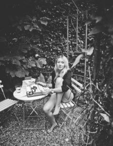 Junge Frau in Gartenlaube mit Schreibmaschine,