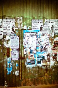 Bretterwand mit abgerissenen Plakaten,
