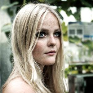 Blonde junge Frau schaut in die Ferne,