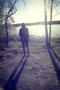 Junge Frau mit langem Schatten an See mit Gegenlicht,