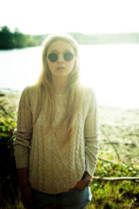 Blonde junge Frau mit Sonnenbrille am See,