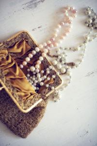 Perlenkette in Abendtasche auf Tisch,