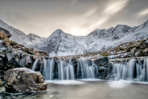View of a waterfall in the wintry Fairy Pools on the Isle of Skye with the snow-capped Black Cullins in the background