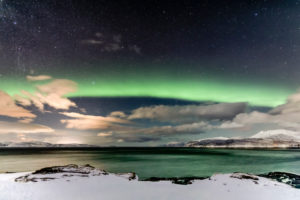 Northern lights by the wintry Kvaenangen Fjord with snow-capped mountains in the background