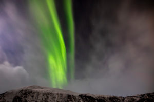 Northern lights in the sky over the snow-capped Lyngen Alps