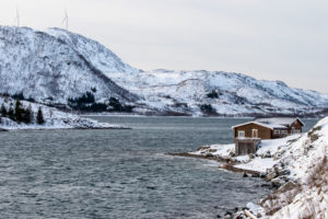 Red wooden house by the wintry fjord in Northern Norway / Troms region