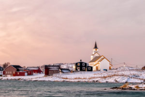 The Hillesoy Church in Brensholmen in Norway in winter at sunset with a fantastic colored sky