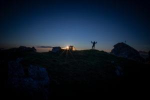Mountaineer with tent on summit, at sunrise, Hoher Burgstall Mountain, Stubai Alps, Tirol, Austria