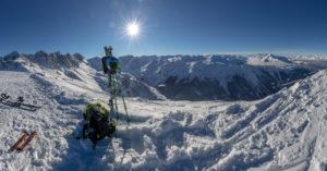 Skitourengeher am Ziel. Ski und Tourenequipment vor Sonne mit Sonnenstern. Bergstation. Schnee.