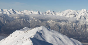 Wintery Tyrolean mountains with a popular touring destination in the foreground. Broken slopes. Country skiing.