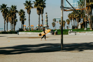 USA, California, Los Angeles, surfer with yellow surfboard on Venice Beach
