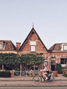 2 female cyclists ride past a residential building, Leiden, Netherlands