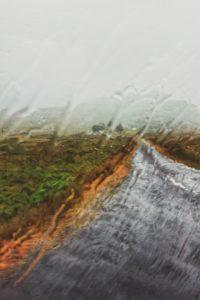 Rain runs down a car window, country road in Ireland