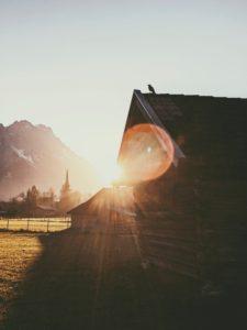 Crow sitting on a hay barn, sunset, field, Wetterstein, Zugspitze