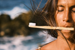 A Beautiful Woman Holds A Bamboo Toothbrush In Her Mouth
