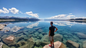New Zealand, person on crystal blue water overlooking Mount Cook