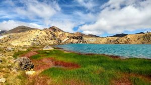Blue lake in volcano crater with green and red grass, Tongariro Crossing in New Zealand