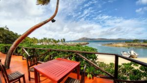 Red table and chairs on terrace on white sand beach, two boats in the sea, Fiji