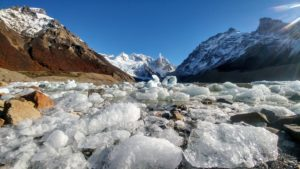 Ice floes in the Laguna Cerro Torre, surrounded by snow-capped mountains in Argentina