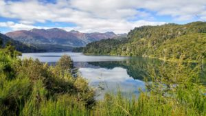Lake surrounded by forest and mountain in the background in Argentina
