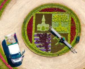 Aerial view of Schloss Berge with baroque garden and bed with city emblem of Gelsenkirchen with gardener who works in the flowerbed with the help of a ladder in Gelsenkirchen in the Ruhrgebiet in North Rhine-Westphalia in Germany, Gelsenkirchen, Ruhrgebiet, North Rhine-Westphalia, Germany