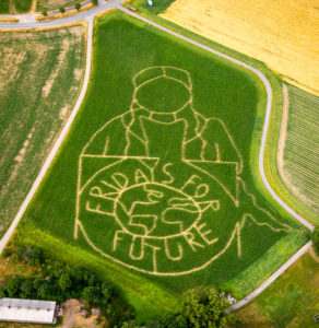 Aerial photograph of the FRIDAYS FOR FUTURE emblem with climate activist Greta Thunberg as corn maze on a field in Cappenberg, Selm, Ruhr area, North Rhine-Westphalia, Germany. The farmer Benedikt Lünemann from Cappenberg near Dortmund realized for the tenth time socially relevant topics on his maize field. He mowed more than 15 hours to create this walk-in 2.5 hectare work of art. Photo: Aerial photograph Hans Blossey, Germany, climate activist Greta Thunberg, the movement Fridays for Future, maize field, maize labyrinth, climate crisis, climate catastrophe, agriculture, maize labyrinth, Cappenberg, emblem FRIDAYS For FUTURE